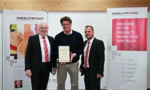 """Mesutronic Geschäftsführer Karl-Heinz Dürrmeier (l.i.B.) und Sales Manager- Export Marco Venditti (r.i.B.) überreichen Lykle Roosjen die Urkunde """"Partner des Jahres 2015""""."""